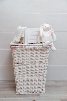 Cesta de mimbre para la ropa en un lavadero. caja de madera blanca y conejito de juguete blanco con vestido rosa