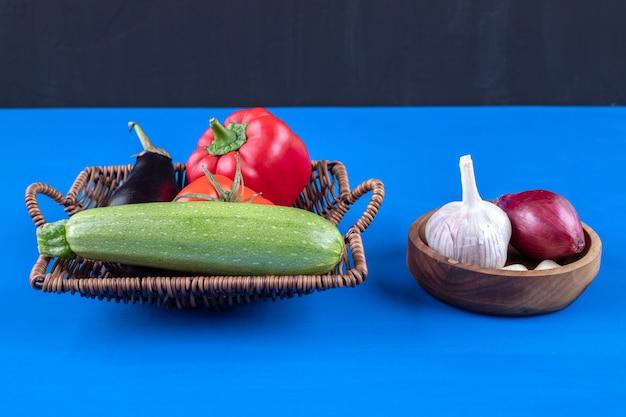 Cesta de mimbre y tazón de fuente de verduras frescas colocadas sobre la superficie azul