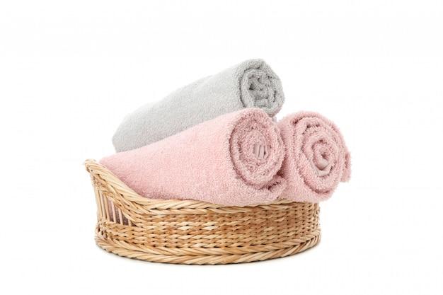 Cesta de mimbre con toallas enrolladas aislado en blanco