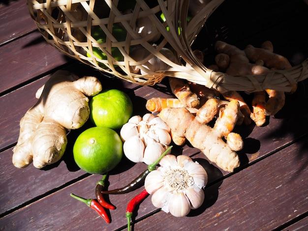 Cesta de mimbre con verduras y hierbas medicinales con limones, jengibre, cúrcuma y ajo en mesa de madera.