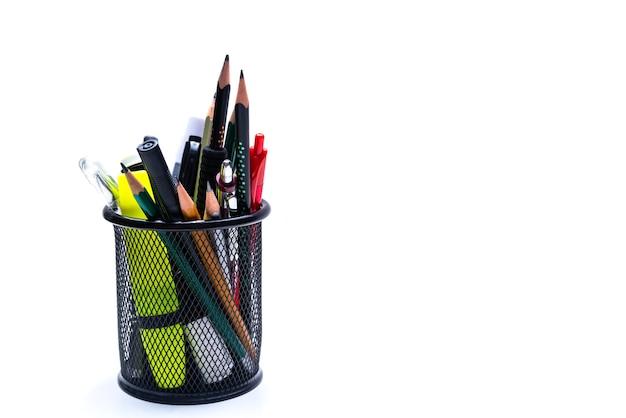 Cesta de oficina con lápices, bolígrafos y marcadores sobre un fondo blanco.