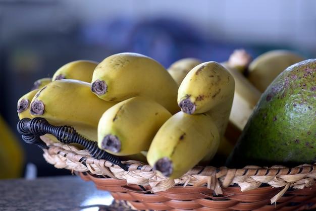 Cesta de paja con racimo de plátanos maduros.