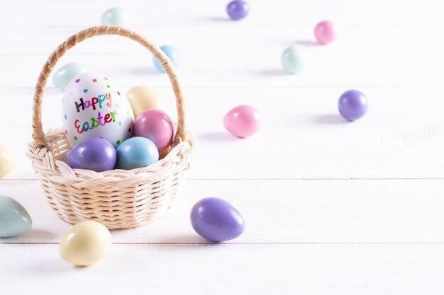 La cesta de pascua llenó de los huevos coloridos en el fondo de madera blanco. copia espacio