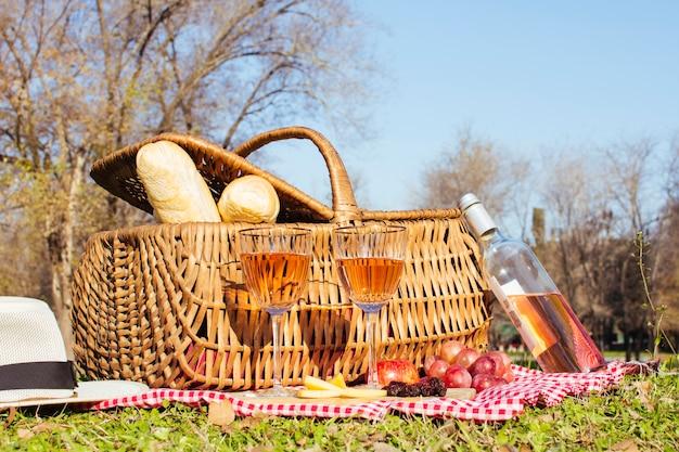Cesta de picnic con botella de vino blanco.