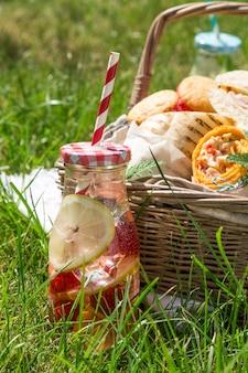 Cesta de picnic con comida en césped verde y soleado