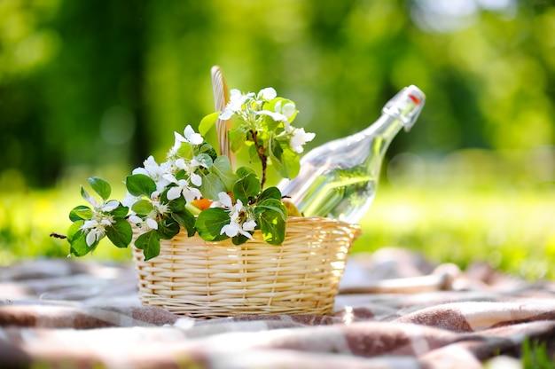 Cesta de picnic con frutas, flores y agua en la botella de vidrio.
