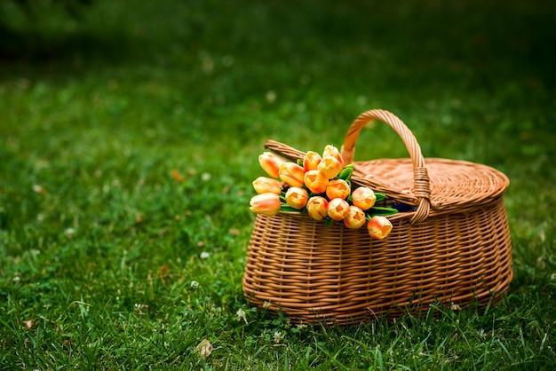 Cesta de picnic con un ramo de tulipanes.
