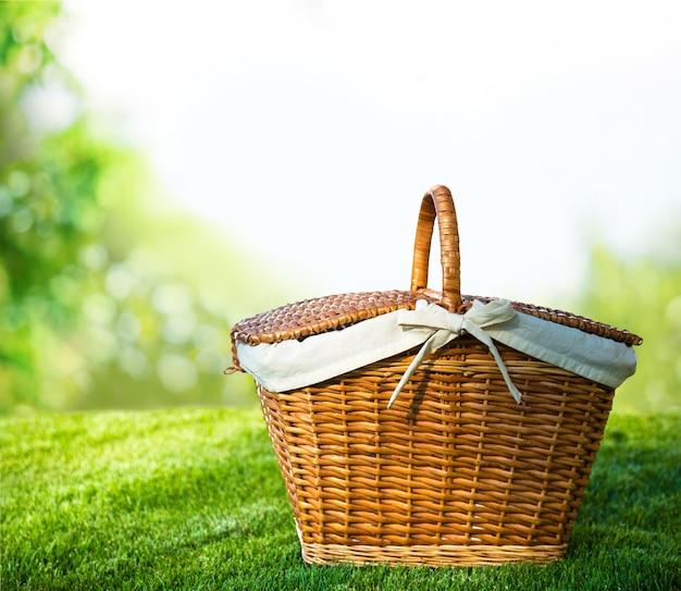 Cesta de picnic con servilleta sobre fondo de naturaleza