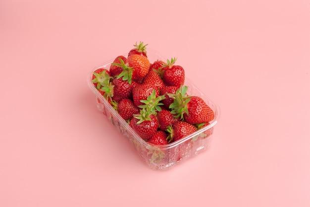 Cesta plástica de fresas sobre fondo rosa pastel