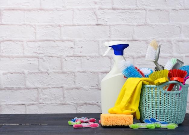 Cesta de plástico azul con cepillos, esponjas y guantes de goma para limpiar, copie el espacio