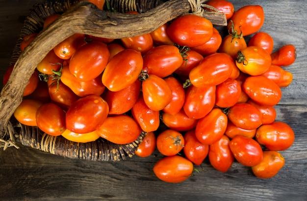 Cesta rebosante de tomates pera en madera rústica