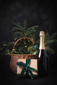 Cesta de regalo navideña con regalo artesanal y vino espumoso en negro.