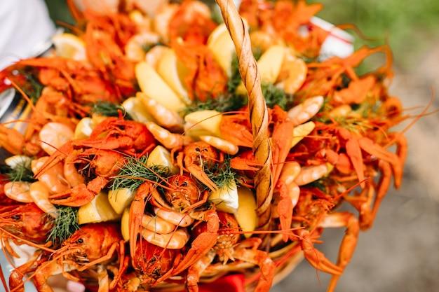 Cesta de regalo tejida festiva para hombre con cangrejos de río y limones