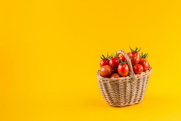 Cesta con tomates sobre un fondo amarillo