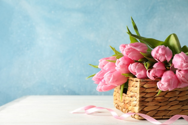 Cesta con tulipanes sobre fondo azul, espacio de copia