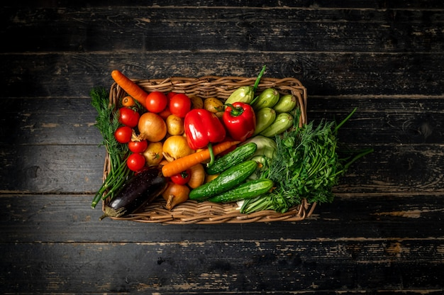 Cesta con verduras frescas patatas, hierbas, repollo, pimientos, zanahorias, pepinos. alimentación saludable