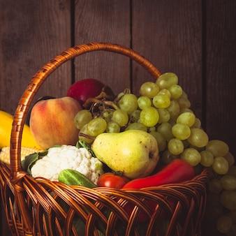 Cesta de verduras y frutas sobre fondo de madera