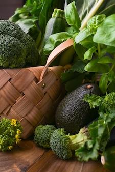 Cesta con verduras verdes frescas sobre un fondo de madera. aguacates, brócoli, cime di rapa otros verdes. espacio libre para texto. copia espacio