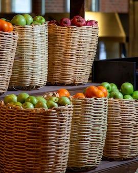 Cestas de fruta de paja rellenas de manzanas, granadas y naranjas.