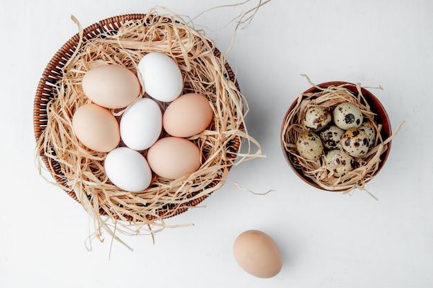 Cestas llenas de huevos en nidos en mesa blanca