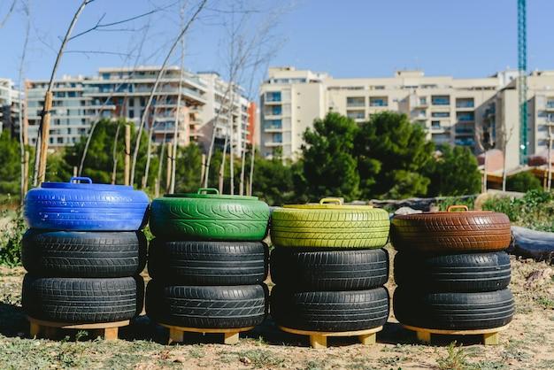 Cestos de basura para reciclar papel, plástico y materiales orgánicos hechos con neumáticos viejos reciclados y colores pintados, concepto de sostenibilidad y reciclaje.