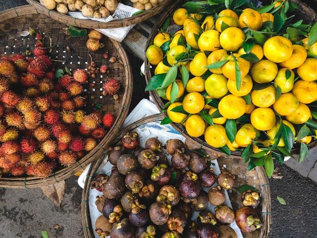 Cestos de rambután, mangostán y tangerines aéreos