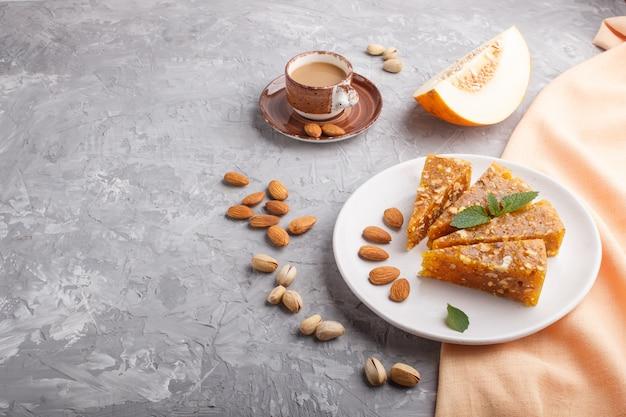 Cezerye tradicional turco de melón caramelizado, pistachos en plato blanco y una taza de café