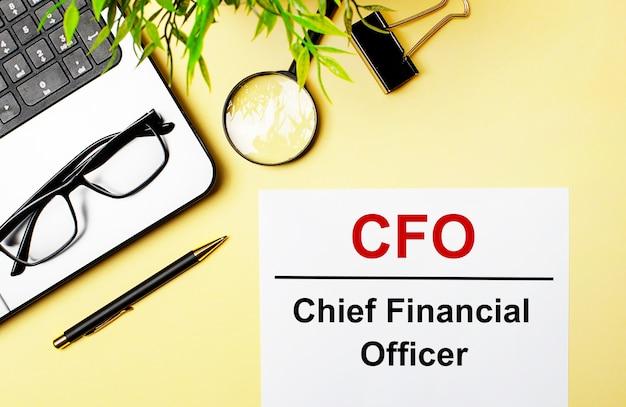 Cfo chief financial officer está escrito en rojo en una hoja de papel blanca sobre una superficie de color amarillo claro junto a una computadora portátil, bolígrafo, lupa, gafas y una planta verde