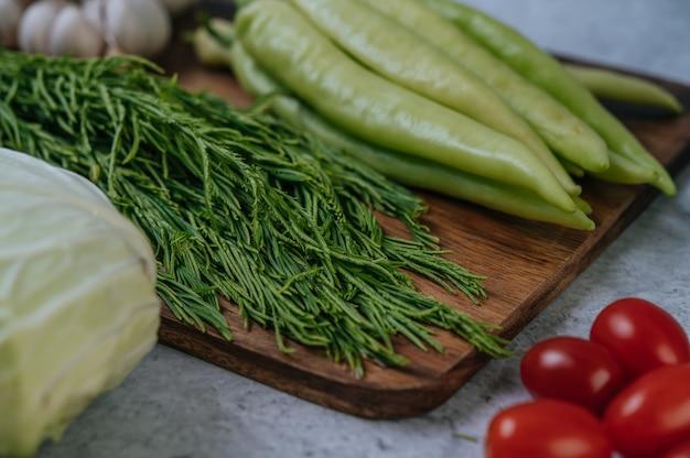 Cha-om, pimiento dulce y ajo en una tabla de cortar de madera.