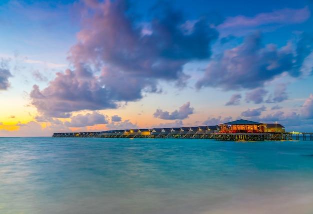 Chalets hermosos del agua en la isla tropical de maldivas en el tiempo de la puesta del sol.