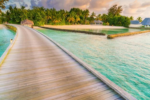 Chalets hermosos del agua en la isla tropical de maldivas en el tiempo de la salida del sol.