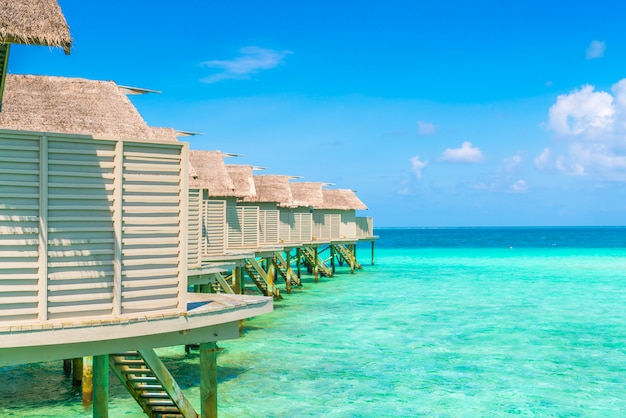 Chalets hermosos del agua en la isla tropical de maldivas.