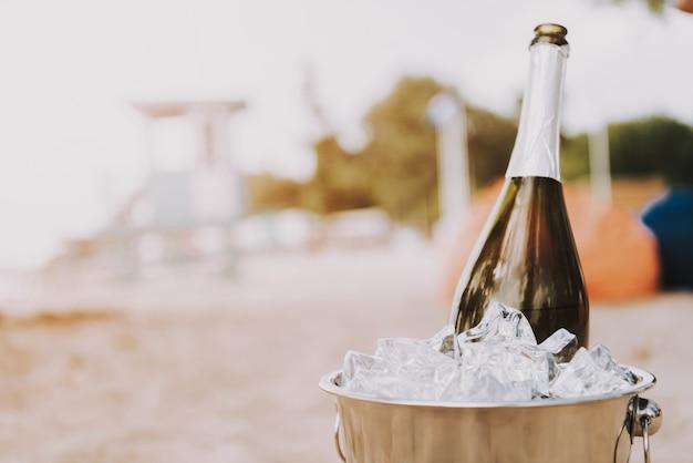 Champagne en el cubo de hielo vacaciones de lujo en la playa