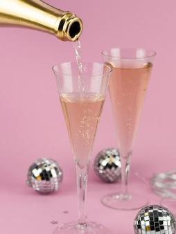 Champagne vertiendo en vaso de botella dorada