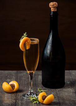 Champán de albaricoque en copa de champán adornado con albaricoques sobre encimera de madera