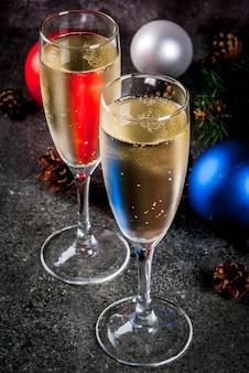 Champán seco en copas, bolas coloridas de navidad, piñas, composición de bodegón de año nuevo sobre fondo de piedra oscura, espacio de copia de enfoque selectivo