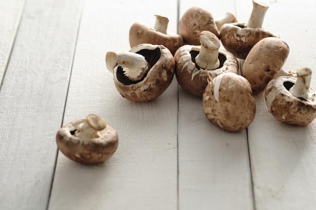 Champiñones de champiñones reales esparcidos sobre un fondo de madera