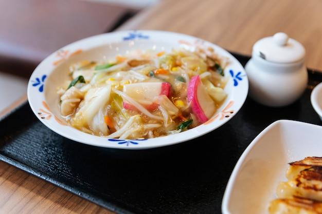 Champon ramen (un plato de fideos que es una cocina regional de nagasaki, japón) con carne de cerdo, camarones, cebollín, brotes, zanahoria, col, maíz y kamaboko.