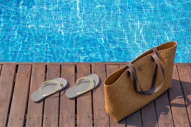 Chanclas y bolsa de playa en la cubierta de madera junto a la piscina.