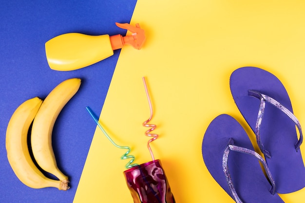 Chanclas cerca de spray y frutas con vaso con pajitas