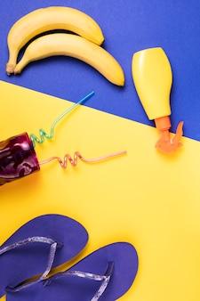 Chanclas cerca de spray y frutas con vidrio