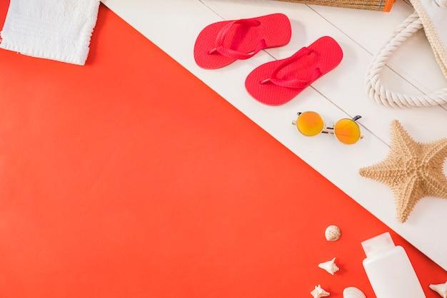 Chanclas cerca de una toalla con estrellas de mar y una botella con gafas de sol entre conchas marinas