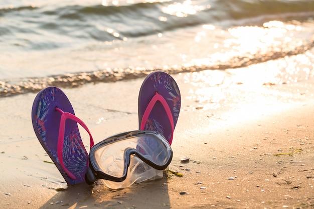 Chanclas coloridas con máscara de buceo en la playa de arena durante el atardecer