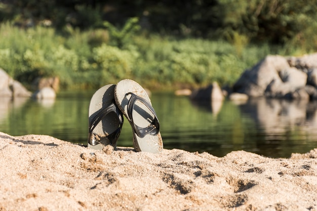 Chanclas en la costa de arena cerca del agua