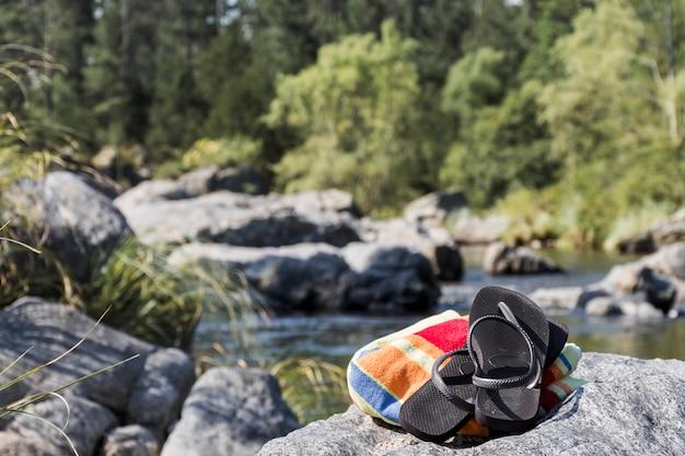 Chanclas en la costa de piedra cerca del agua