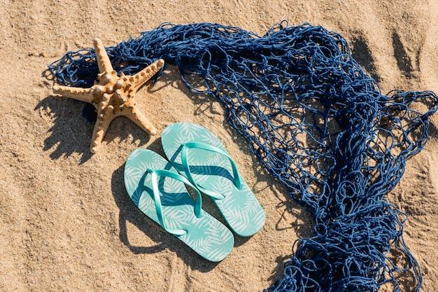 Chanclas y estrellas de mar con malla sobre arena.