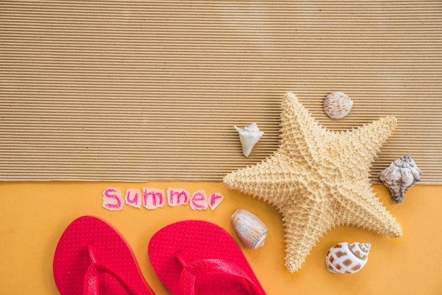 Chanclas y palabra de verano cerca de la estera con estrellas de mar y conchas marinas