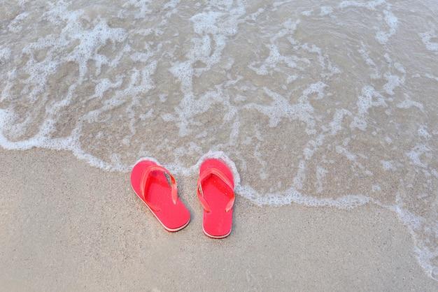 Chanclas en la playa con mar de olas de arena en el mar