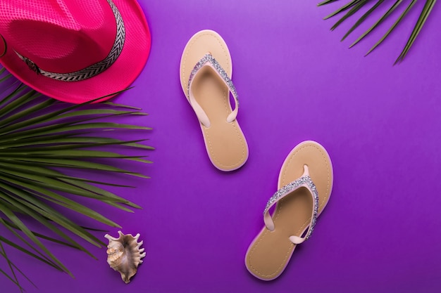Chanclas de playa de mujer hermosa en el fondo violeta o púrpura. concepto de verano de playa y concepto de vacaciones, vista superior