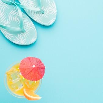 Chanclas y refrescante cóctel sobre fondo de color